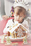 Girl decorates gingerbread house Stock Image