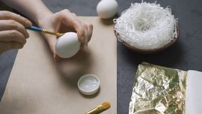 Girl decorates gold eggs for Easter.  stock video