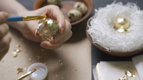 Girl decorates gold eggs for Easter.  stock footage