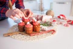 Girl decorates New Year celebration cupcakes Royalty Free Stock Image