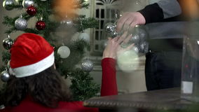 Girl decorating big Christmas tree while guy helps. Young romantic couple decorating Christmas tree by a fireplace with red and silver ornaments, red, blue and stock video footage