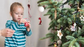 Girl decorating christmas tree. Authentic family xmas time concept Stock Image