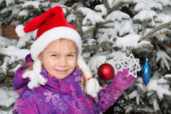 Girl Decorating Christmas Tree. Cute young girl in santa hat decorating real christmas tree covered with snow stock images