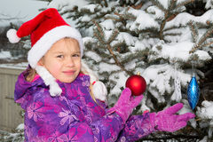Girl Decorating Christmas Tree. Cute young girl in santa hat decorating real christmas tree covered with snow royalty free stock photo