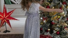 The girl is decorating a Christmas tree in a flattering dress with a train. Christmas interior. The girl is decorating a Christmas tree in a flattering dress stock video footage