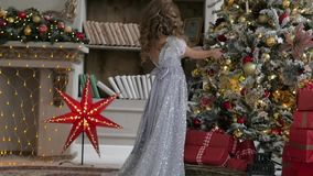 The girl is decorating a Christmas tree in a flattering dress with a train. Christmas interior. The girl is decorating a Christmas tree in a flattering dress stock video