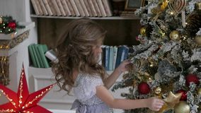 The girl is decorating a Christmas tree in a flattering dress with a train. Christmas interior. The girl is decorating a Christmas tree in a flattering dress stock footage