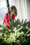 Girl decorating a Christmas tree Stock Photos