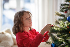 Girl decorating a Christmas tree Royalty Free Stock Images