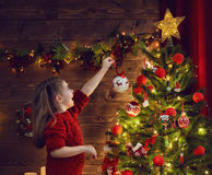 Girl is decorating the Christmas tree Royalty Free Stock Image
