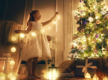 Girl is decorating the Christmas tree. Merry Christmas! Cute little child girl is decorating the Christmas tree royalty free stock images