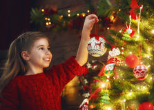 Girl is decorating the Christmas tree Royalty Free Stock Images