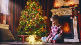 Girl is decorating the Christmas tree Royalty Free Stock Photography