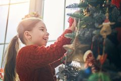 Girl is decorating Christmas tree Stock Images