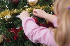 Girl decorating the Christmas tree,shot from behind Stock Image