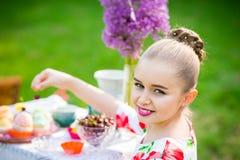 Girl decorating cupcakes in backyard. Little girl decorating cupcakes in in the backyard Royalty Free Stock Photos