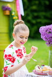 Girl decorating cupcakes in backyard. Little girl decorating cupcakes in in the backyard Royalty Free Stock Photo