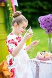 Girl decorating cupcakes in backyard. Little girl decorating cupcakes in in the backyard Stock Image