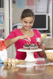 Girl Decorating Homemade Cupcakes In Kitchen Stock Photo