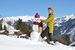 Girl decorating a snowman Royalty Free Stock Photo