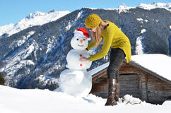 Girl decorating a snowman Royalty Free Stock Images