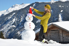 Girl decorating a snowman Stock Photos