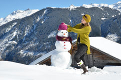 Girl decorating a snowman Royalty Free Stock Image