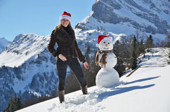 Girl decorating a snowman Stock Photo