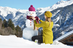Girl decorating a snowman Stock Images