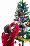 Girl decorating Xmas tree Stock Photos
