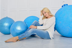 The girl and decorative Christmas balls. A young girl is sitting on the floor leaning on large decorative Christmas balls blue Stock Images