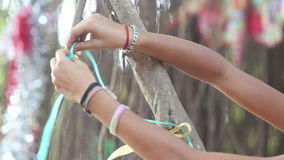 Girl decorator tying ribbons on the branches stock video