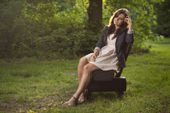 Girl deep in thoughts sitting on a bench in park royalty free stock image