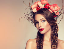 Girl with delicate wreath from flowers, fruits and twigs on her head. stock photo