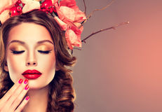Girl with delicate wreath from flowers, fruits and twigs on her head. Hair braided in thick pigtails, vivid make-up and bright-red lipstick on the lips Stock Photos