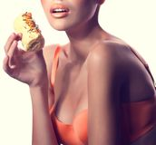 Girl with delicious orange praline Stock Images