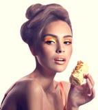 Girl with delicious orange praline Stock Photos