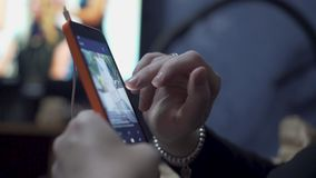 The girl delves into the smartphone by controlling it using the touch screen. Close-up of the girl`s hand.