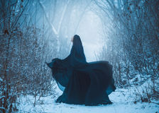 The girl a demon walks alone. She is wearing a long, black traveling cloak Royalty Free Stock Image