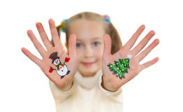 Girl demonstrating Christmas symbols painted on her hands. Snowman and Christmas tree Royalty Free Stock Photos