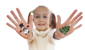 Girl demonstrating Christmas symbols painted on her hands. Snowman and Christmas tree Royalty Free Stock Photography
