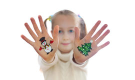 Girl demonstrating Christmas symbols painted on her hands. Snowman and Christmas tree Royalty Free Stock Photo