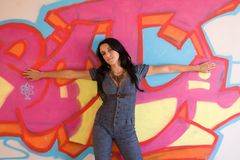 Girl in Denim CatSuit. A girl wearing a denim catsuit leaning against a graffiti wall royalty free stock images