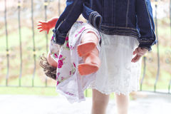 Girl with denim coat and spring dress stepping out with doll Royalty Free Stock Image