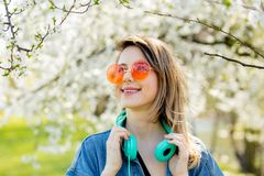 Girl in a denim jacket and headphones near a flowering tree royalty free stock images