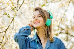 Girl in a denim jacket and headphones stands near a flowering tree royalty free stock image