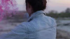 Girl in denim jacket inflates colored smoke bombs stock footage