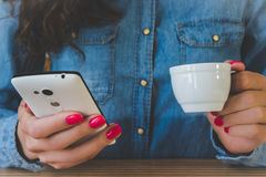 Girl in a denim shirt drinking coffee and enjoys the phone. The girl in the blue denim shirt sitting at the table. In one hand a white Cup of espresso, and the Royalty Free Stock Image