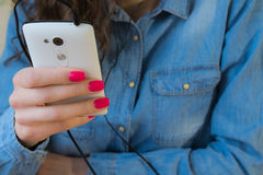 Girl in a denim shirt listens to music on the white phone. The girl in blue denim shirt with red nail Polish listens to music on a white phone Stock Image