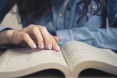 Girl in a denim shirt is reading a book. Girl in a denim shirt and white t-shirt sitting at a table and reading a book. The girl purple manicure. Close up photo Stock Images